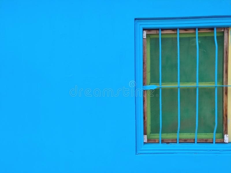 Blue-painted wall and old frame window. Blue-painted wall and old frame window royalty free stock photo