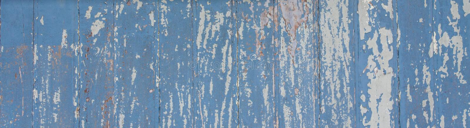 Blue painted wooden wall plank to the frame as simple peeling paint timber old grungy weathered wood surface texture background. Blue painted wooden wall plank royalty free stock photo
