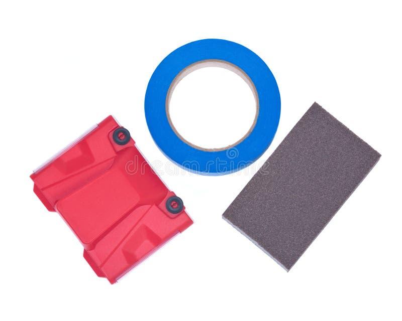 Blue painter`s tape, jumbo sanding sponge and paint trimline edger royalty free stock photo