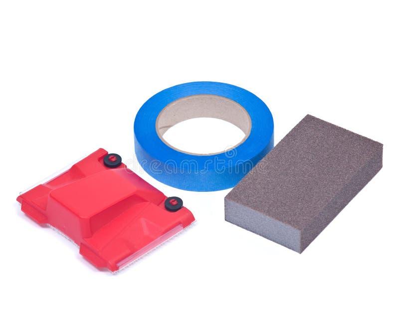 Blue painter`s tape, jumbo sanding sponge and paint trimline edger royalty free stock image
