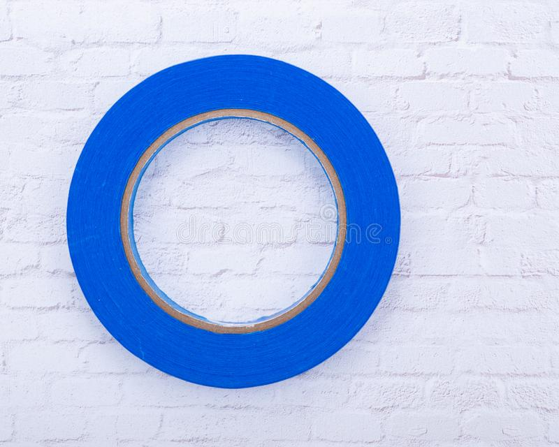 Blue Painter`s Tape for multi surfaces isolated on white brick wall royalty free stock photo