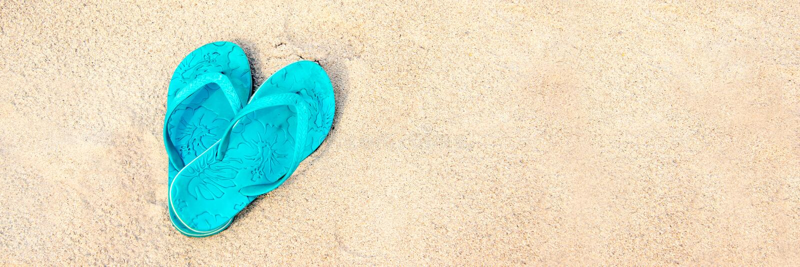 Blue pair of flip flops on the beach panoramic summer concept. Blue pair of flip flops on the beach, panoramic summer concept stock images