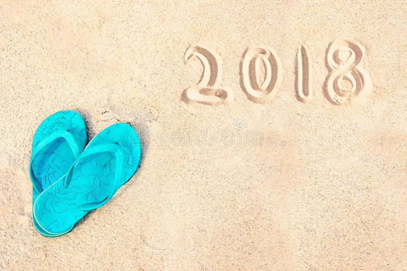Blue pair of flip flops on the beach, 2018 written in the sand. Blue pair of flip flops on the beach with 2018 written in the sand royalty free stock images