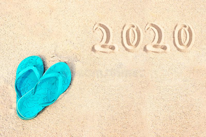 Blue pair of flip flops on the beach, 2020 written in the sand. Tropical new year holiday card. Blue pair of flip flops on the beach, 2020 written in the sand stock photography