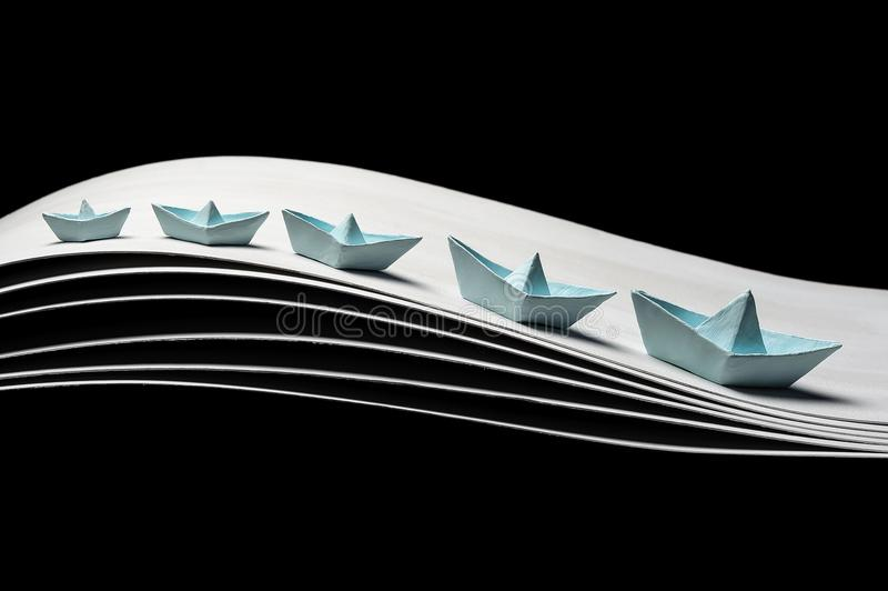 Paper blue boats on waves on a black background royalty free stock photo
