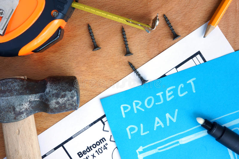 Blue paper with home improvement project plan, tools kit. On a wood background royalty free stock image