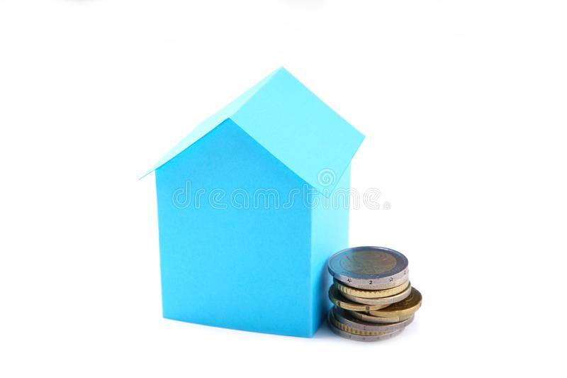 Blue paper house with coins isolated on white background royalty free stock photos