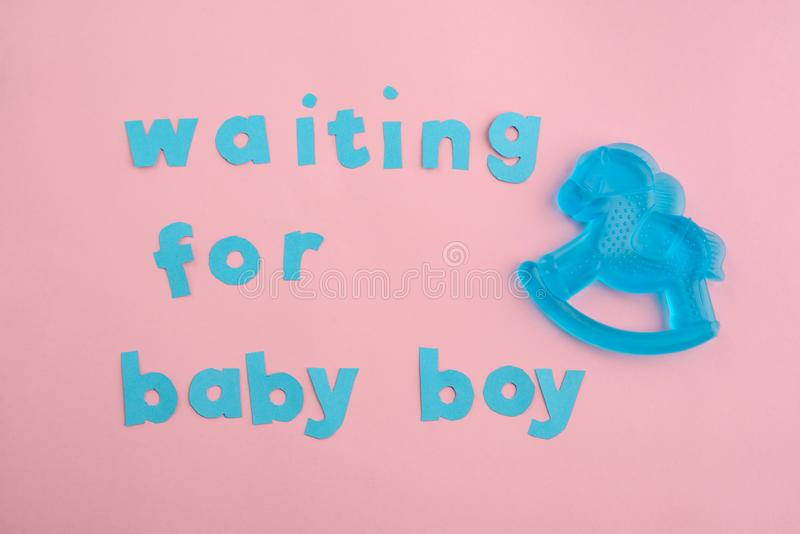 Blue paper letter and teether. On pink background. Baby shower decor idea. Anticipation of giving birth to a baby boy royalty free stock photos