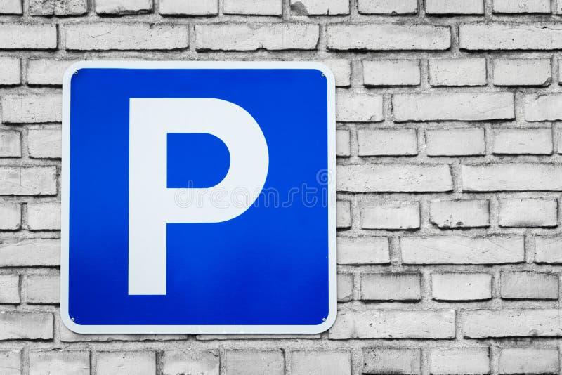 Blue parking sign on black and white bricks stock photos