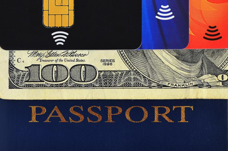 Blue passport, one hundred dollars bill and three different credit cards stock photos