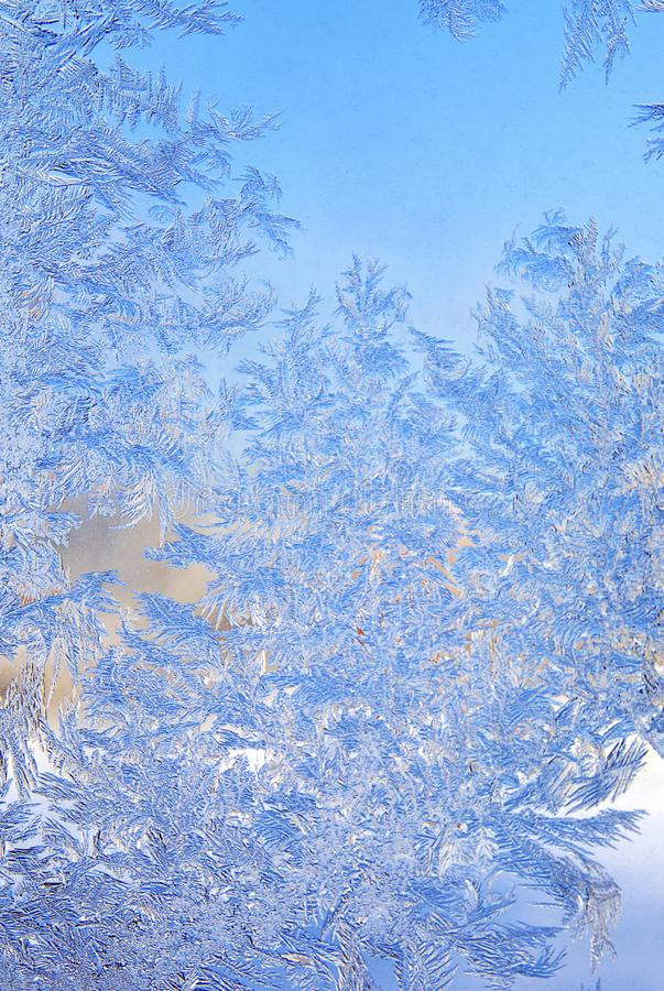 Blue patterns on window. Picture blue texture patterns from crystals of frozen water on the window frosty winter day in Christmas closeup on the blurry royalty free stock images