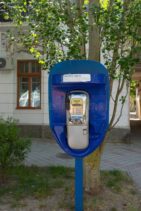 Blue pay phone on the street background stock photography