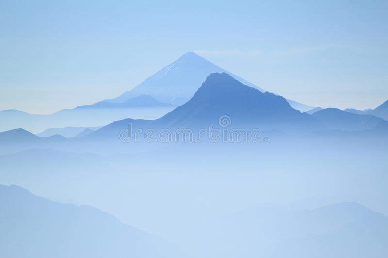 Blue peaks in mountains on blue sky. Two peaks in blue colour in high mountains during treking to the peak Alam Kuh at dawn. Early morning clear blue sky. In the royalty free stock image