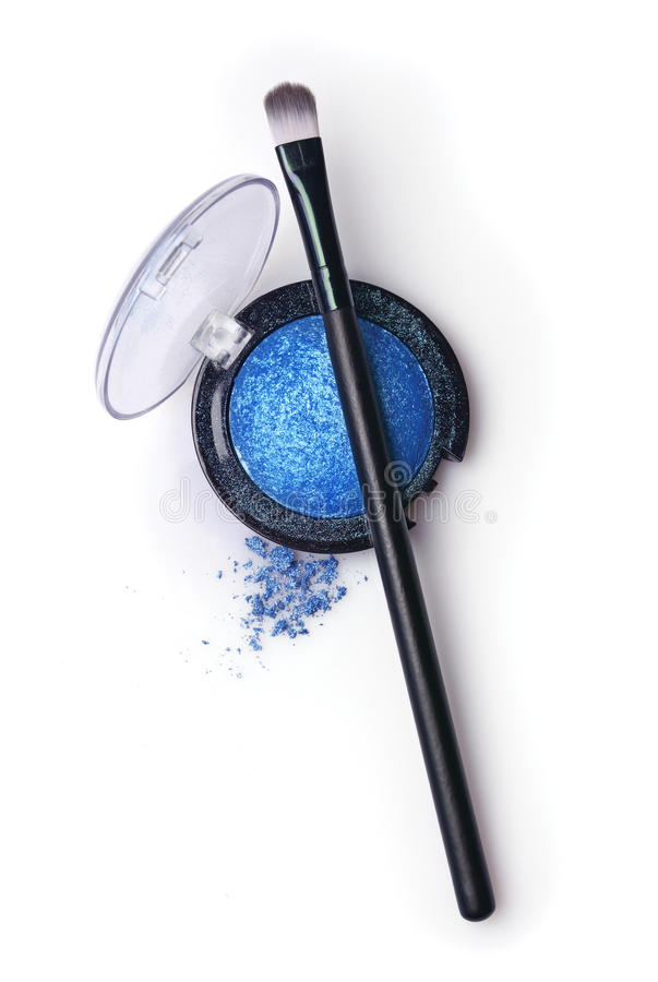 Blue pearlescent eyeshadow and brush for makeup stock photography