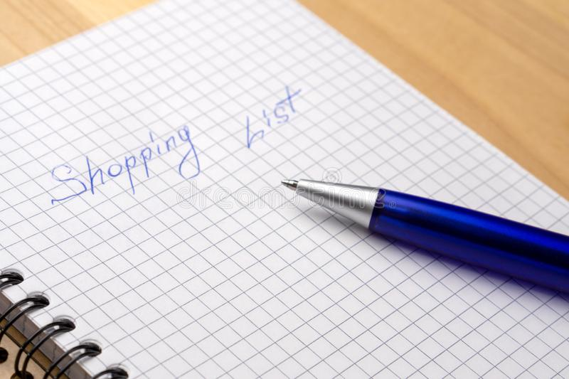 Blue pen on a notebook with sheets in a cage. Sign Shopping List. Close-up royalty free stock photo