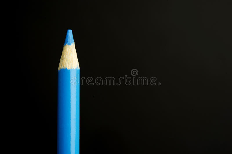 Blue pencil crayon on a black background royalty free stock image