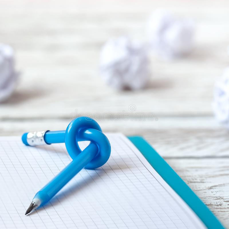 Blue Pencil with knot on writing pad on white wood background stock image