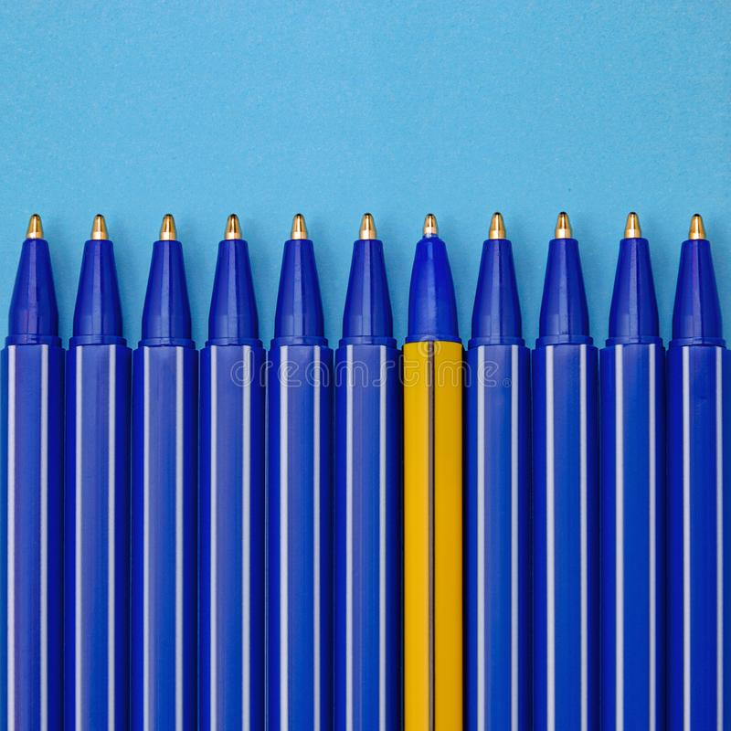 Blue pens and one different on blue background. Individuality concept. stock photography