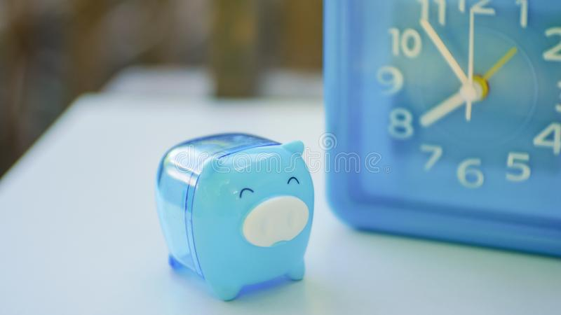 Blue pig and blue clock. In saving money concept royalty free stock photos