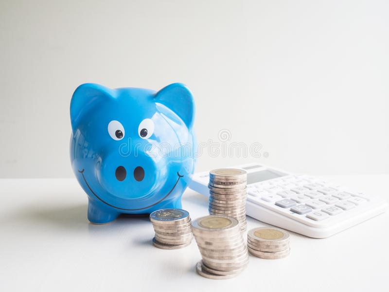 Blue Piggy bank and calculator  with coins pile, Saving money for future plan and retirement fund concept.  stock images