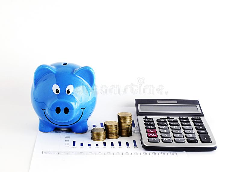 Blue piggy bank and calculatr money coins for loans concept. Close up of Blue piggy bank and calculatr money coins for loans concept royalty free stock photos