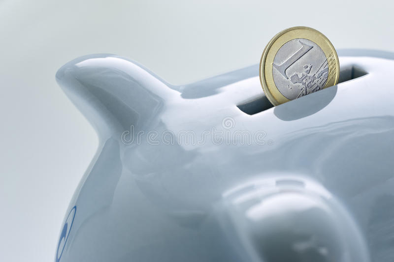 Blue piggy bank and a coin falling in it. Closeup royalty free stock images