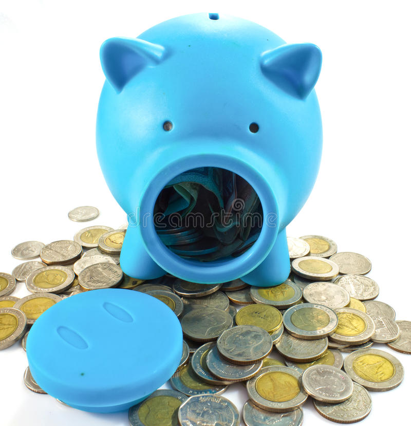 Blue piggy bank with coins. Blue piggy bank with some coins royalty free stock images