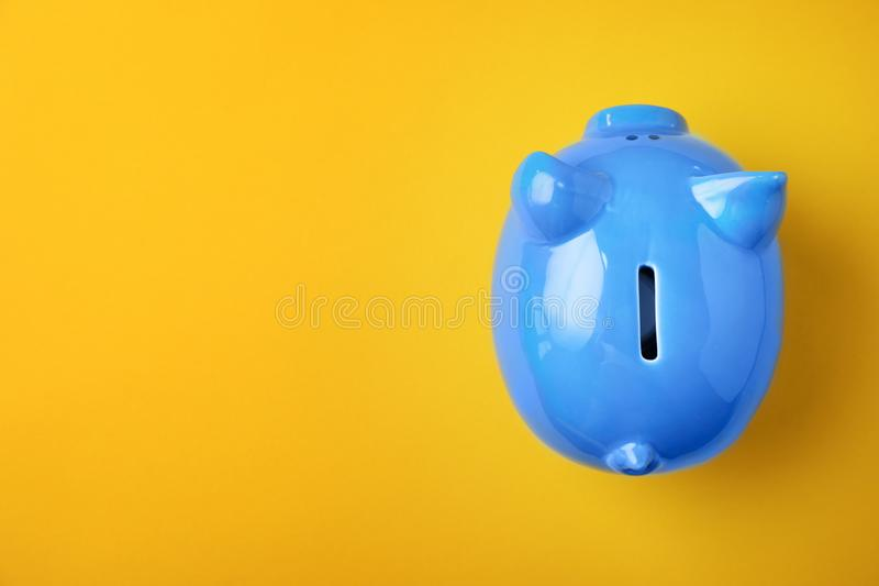 Blue piggy bank on color background. Top view stock photos