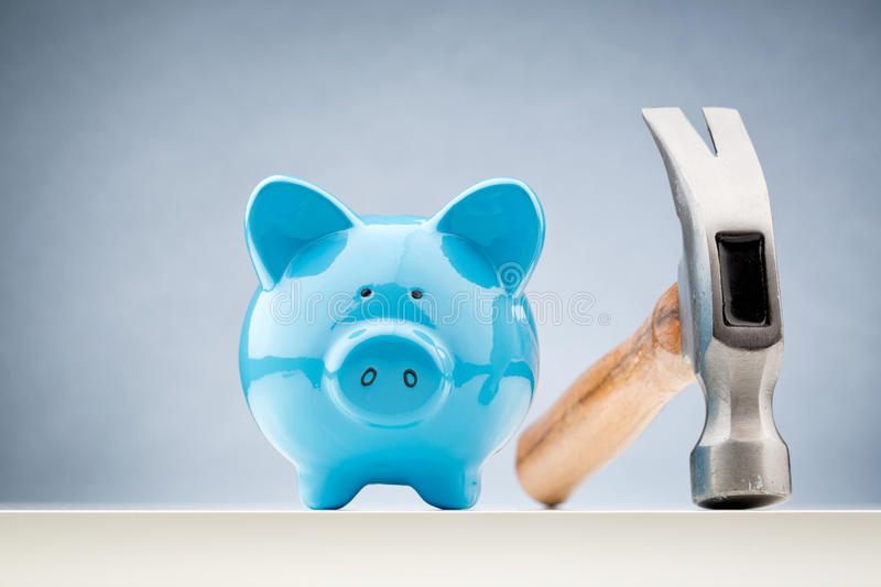 Blue Piggy Bank and a Hammer. Front view of a blue piggy bank with a hammer next to it royalty free stock photo