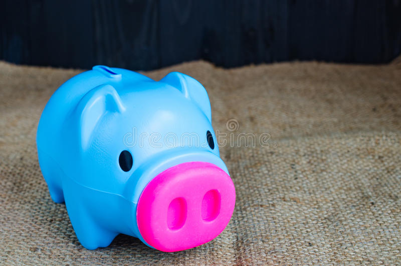 Blue piggy bank on hemp background. Saving concept stock photography