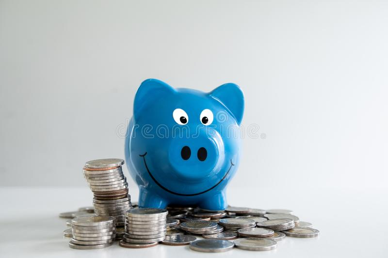 blue piggy bank saving and prevent money with coins pile, step up growing business to success and saving for retirement concept stock photos