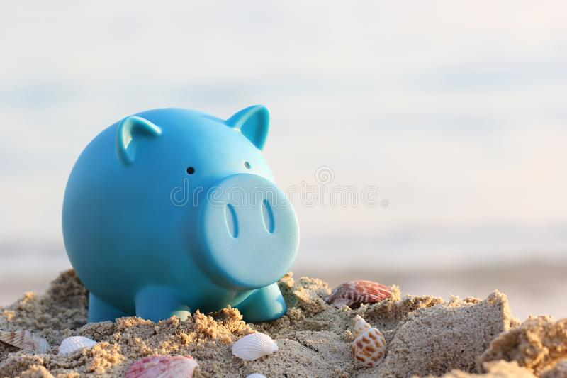 Blue piggy bank on sea beach, Saving planning for Travel budget of holiday concept.  stock photos