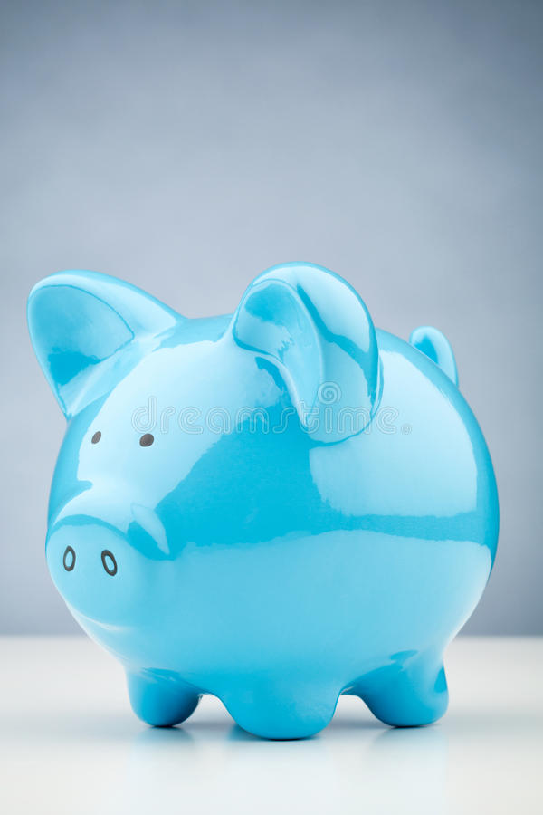 Blue Piggy Bank. A blue piggy bank standing on a white desk surface with copy space on the background royalty free stock photo