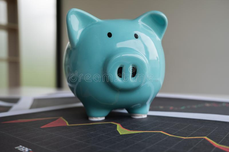 Blue piggy bank with stock graph, step up growing business to success and saving for retirement concept.  stock images