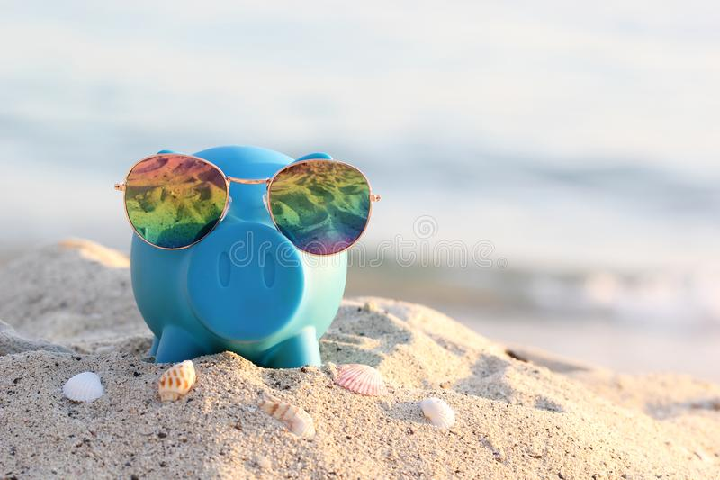 Blue piggy bank with sunglasses on sea beach, Saving planning for Travel budget of holiday concept stock photo