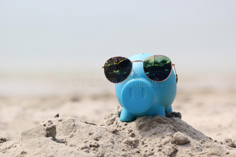 Blue piggy bank with sunglasses on sea beach, Saving planning for Travel budget of holiday concept.  royalty free stock photos