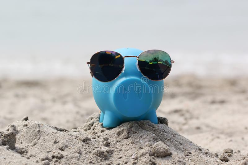 Blue piggy bank with sunglasses on sea beach, Saving planning for Travel budget of holiday concept.  stock photos