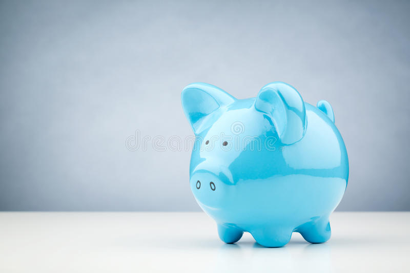 Blue Piggy Bank on a Table. Horizontal image of a blue piggy bank standing on a white desk surface with copy space on the background stock photo