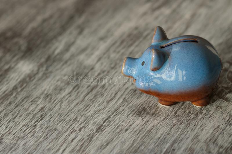 Blue piggy bank on the wooden background. Soft focus background royalty free stock image