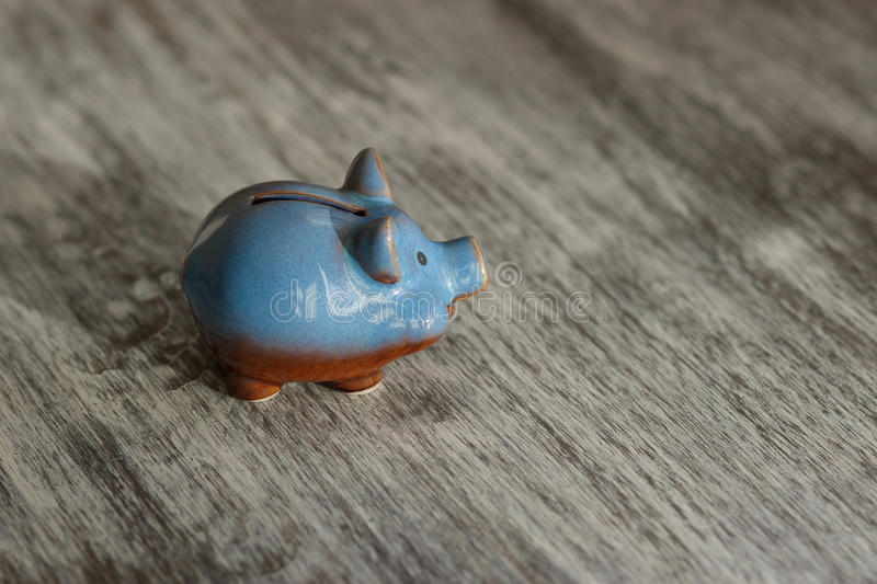 Blue piggy bank on the wooden background. Soft focus background royalty free stock images