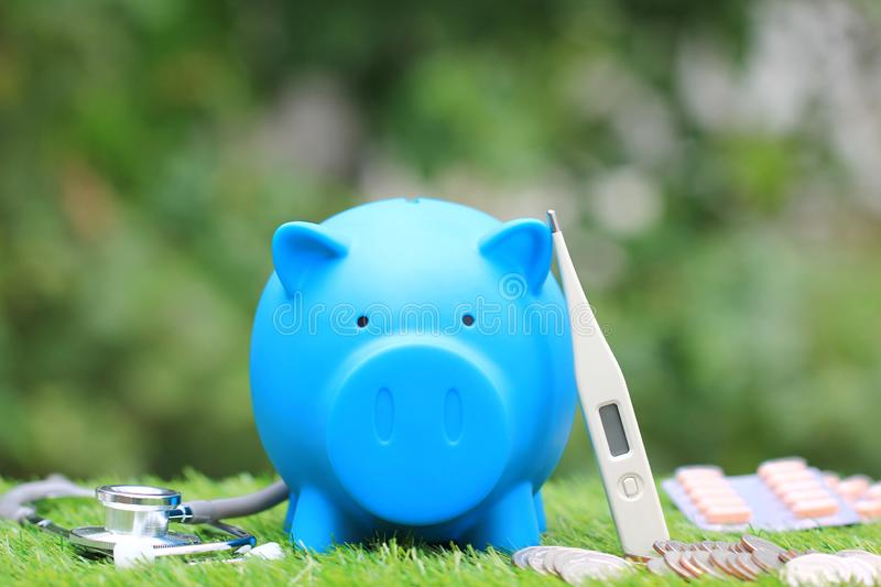 Blue piggy with thermometer and medicine on natural green background,Save money for Medical expenses and Health care concept. royalty free stock images