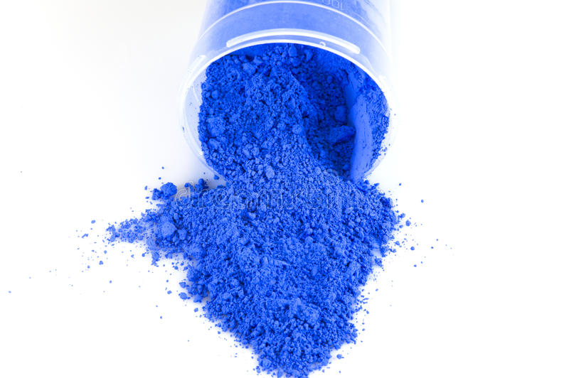 Blue Pigment. Powder spilling from a bottle on a white surface royalty free stock photography