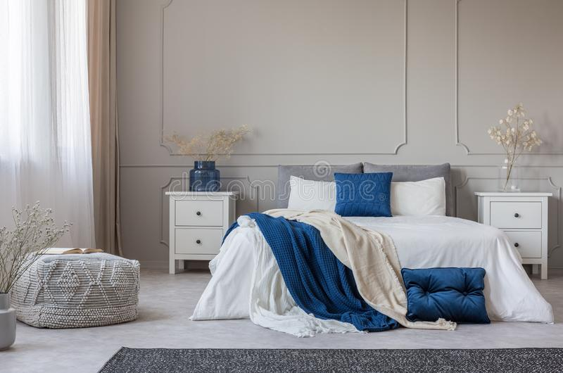 Blue pillow and blanket on white bed in spacious bedroom interior, copy space on empty grey wall stock image