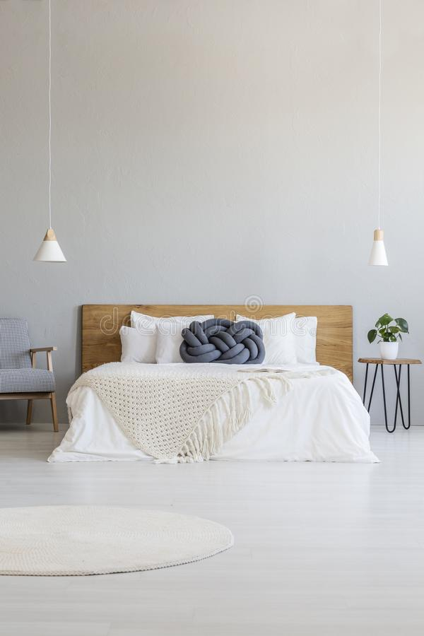 Blue pillow on white bed with wooden headboard in hotel bedroom. Interior with lamps. Real photo stock photo