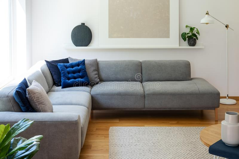 Blue pillows on grey corner sofa in apartment interior with lamp and plant next to poster. Real photo. Concept royalty free stock photo