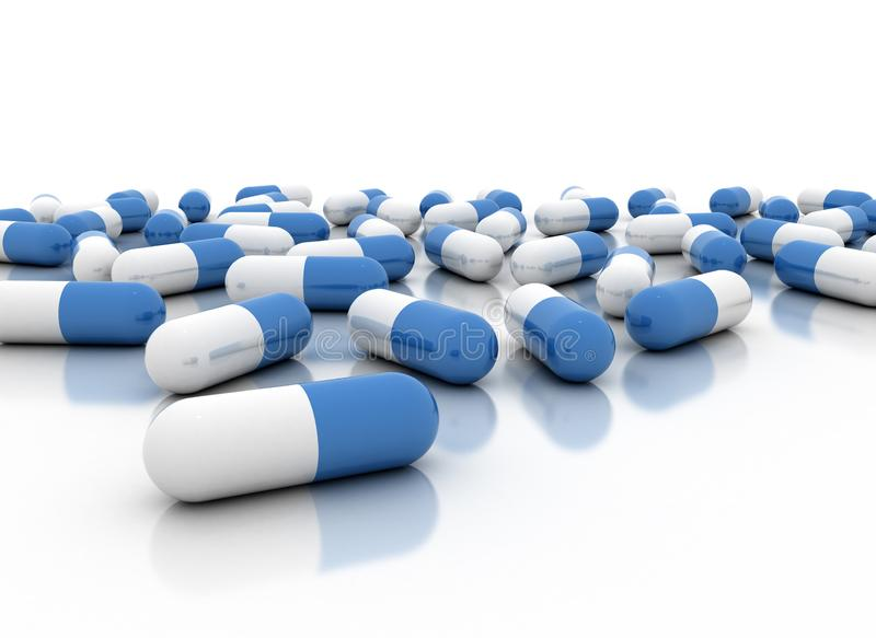Blue pills and capsules scattered on white reflective background royalty free stock images