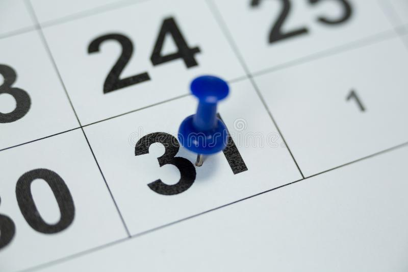 Blue pin push on day 31st of month end on white calendar royalty free stock images