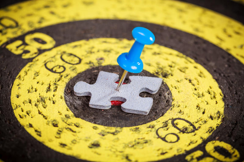Blue pin stuck to man shape jigsaw puzzle piece on old target board stock images