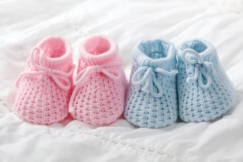 Blue and pink baby booties. On white background royalty free stock image
