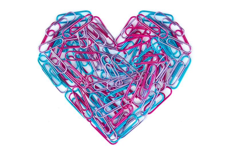 Blue and pink paper clips arranged in heart shape. On white background stock photo